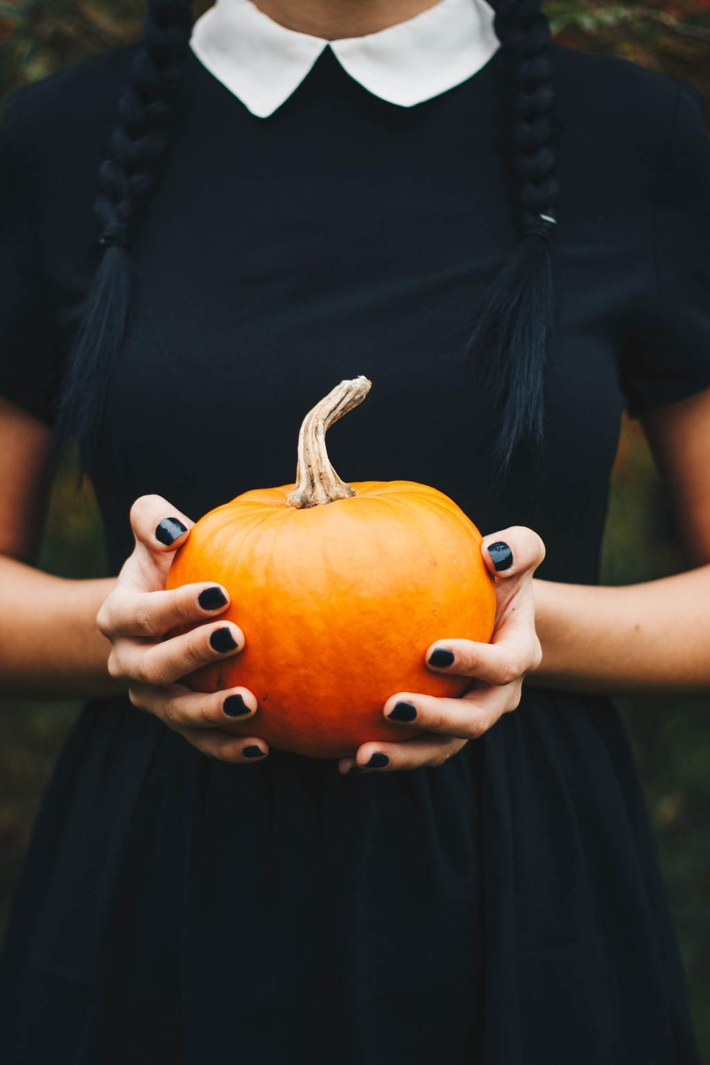 Black dress halloween costume - girl wearing a black dress holding a pumpkin