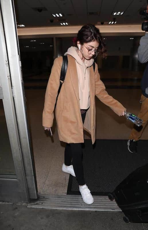 Sarah Hyland wearing a nude cropped hoodie, a camel colored mid-length coat, black leggings, hoop earrings, a black leather backpack, and white low-top sneakers