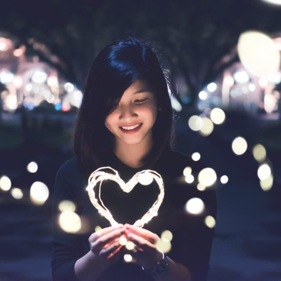 Girl holding light-up heart at night