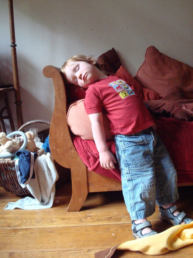 A kid sleeping, standing up