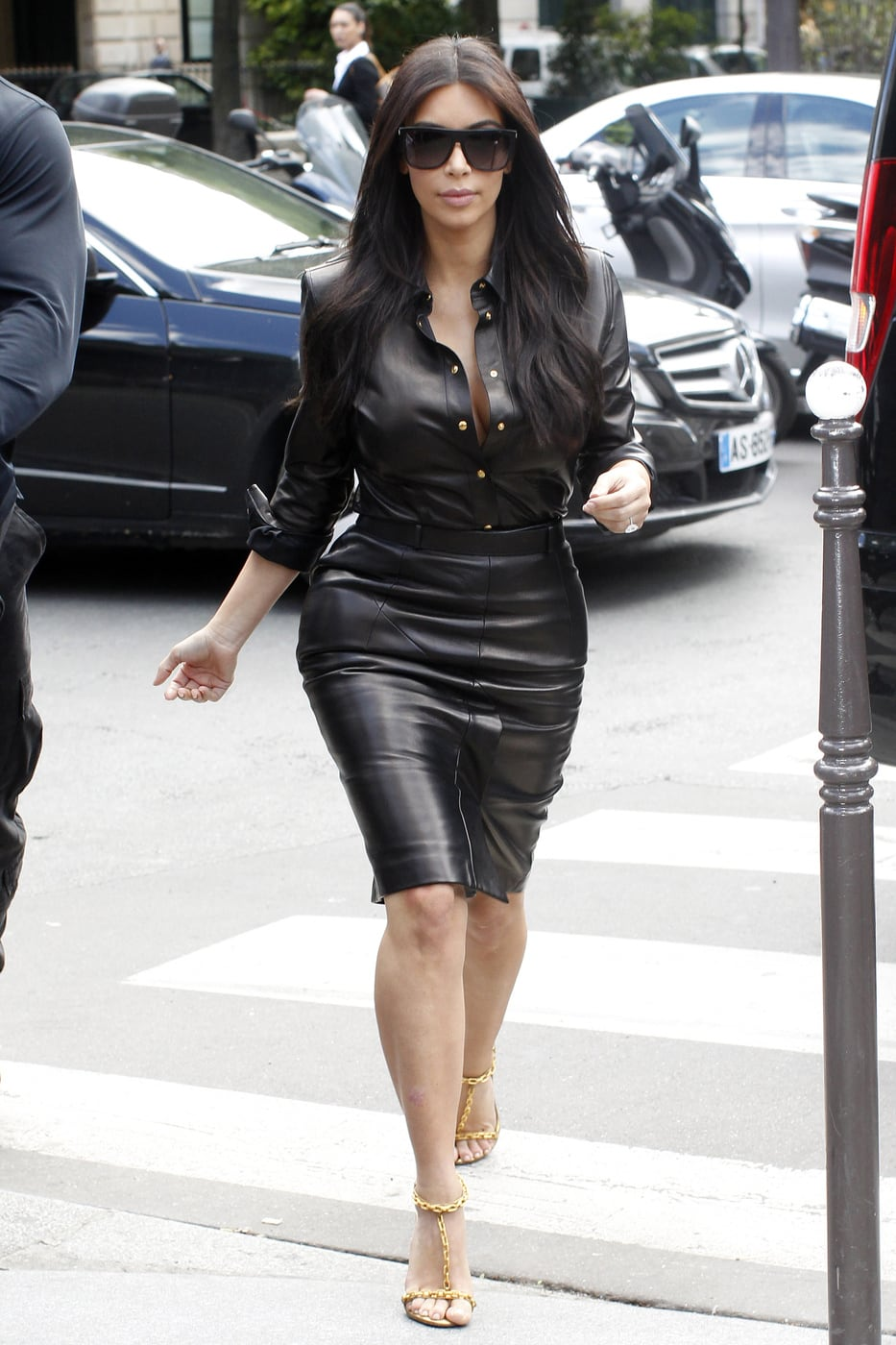 Celebrity fashion: Kim Kardashian wearing a black leather skirt and black leather button down shirt, oversized sunglasses, and gold chain heels