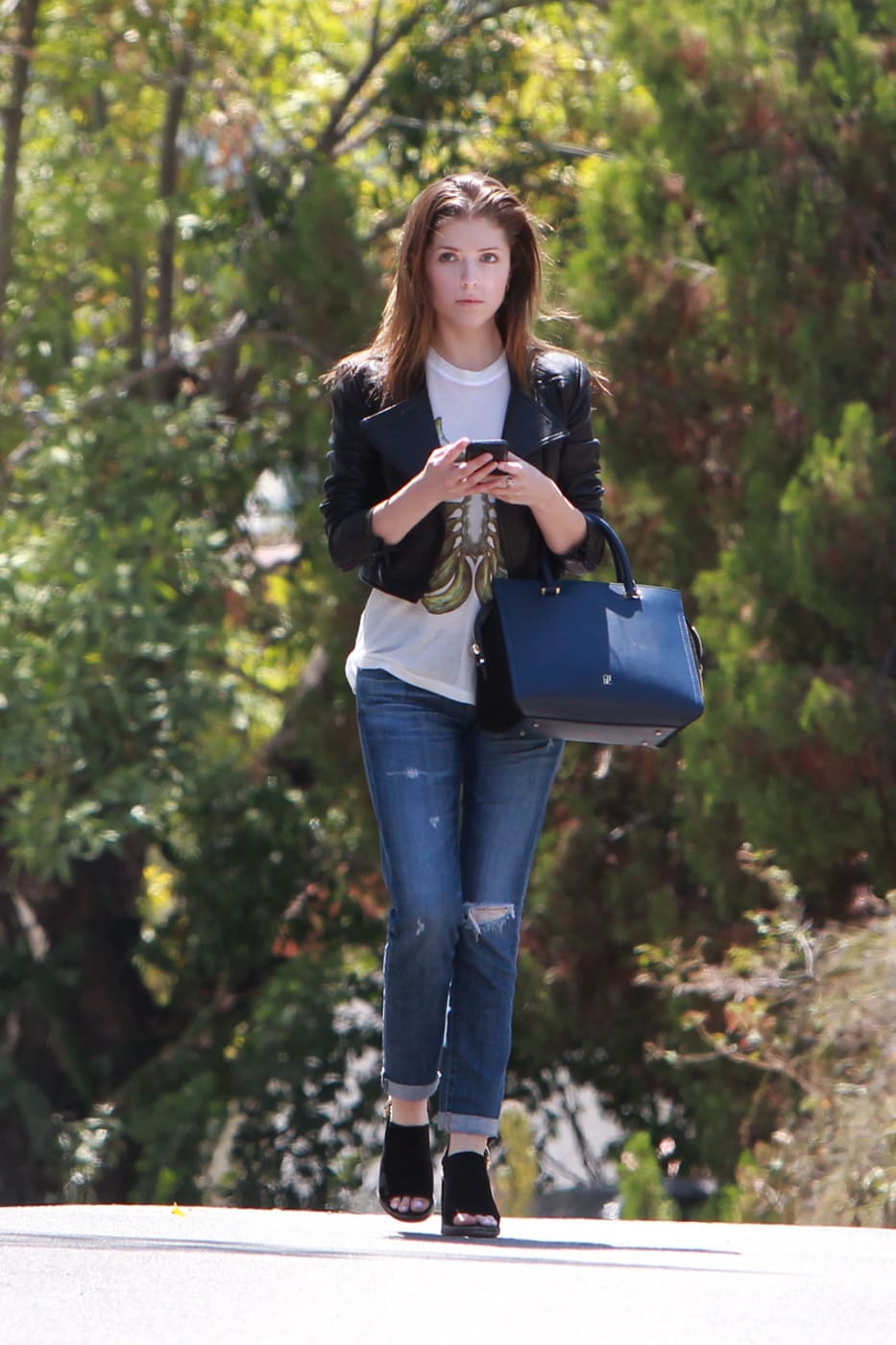 Celebrity fashion: Anna Kendrick wearing cuffed jeans, a cropped moto jacket, a graphic tee, blue purse, and black slip on wedges