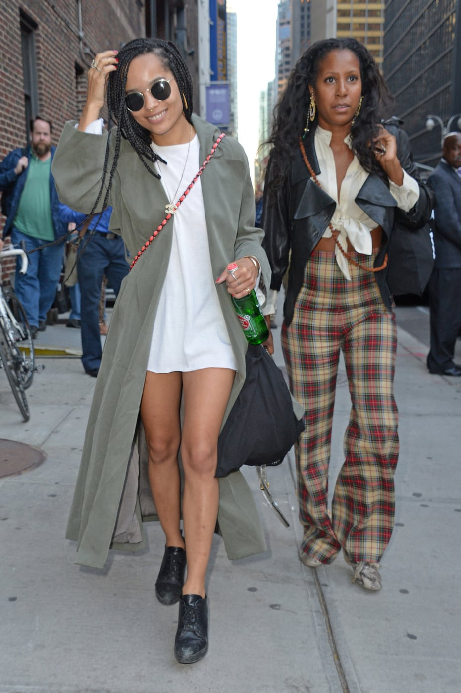 Celebrity fashion: Zoe Kravitz wearing a white tee shirt dress, an oversized army green trench coat, a Chanel crossbody bag, and black oxford heels