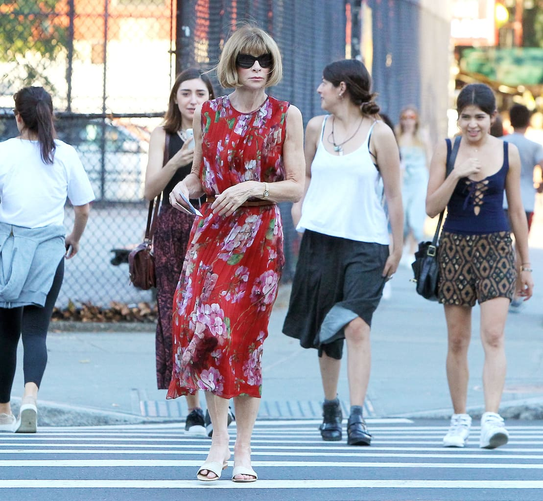 Anna Wintour wearing a red floral dress while crossing the street