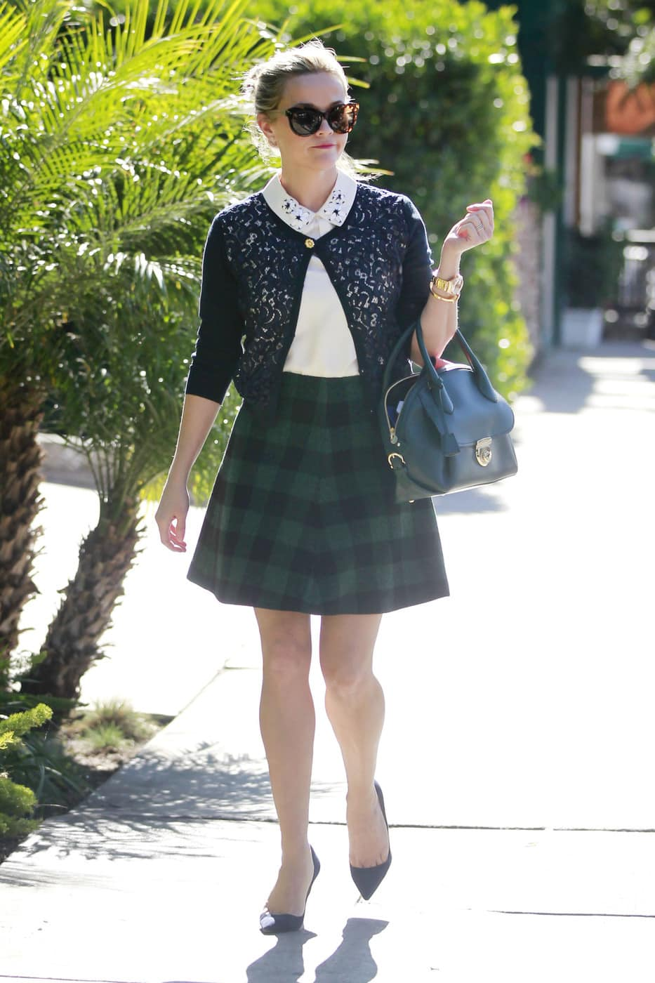 Celebrity fashion: Reese Witherspoon wearing a plaid skirt, cropped lace cardigan, detailed collar shirt, and pointed toe heels with oversized sunglasses and a turnlock purse