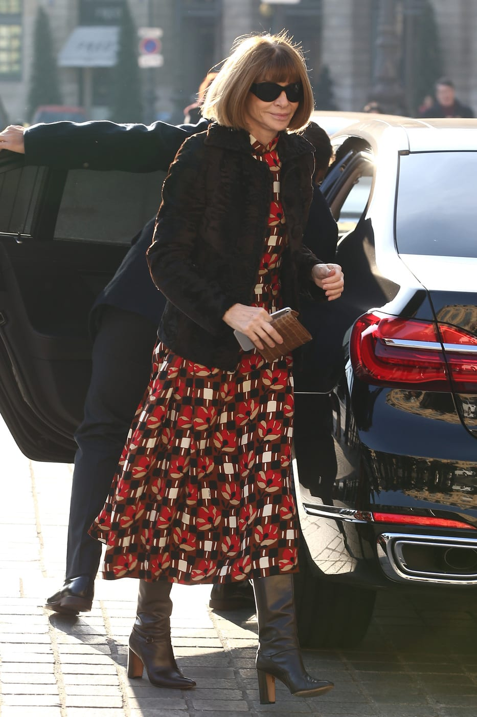 Anna Wintour wearing a red patterned dress, black boots, and a puffy coat
