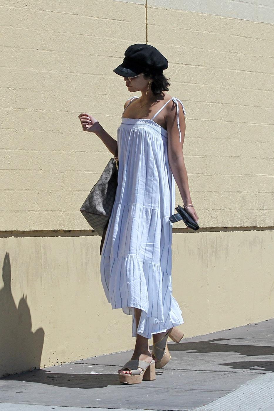 Celebrity fashion: Vanessa Hudgens wearing a white linen dress, oversized tote bag, baker boy cap in black, and chunky platform heels