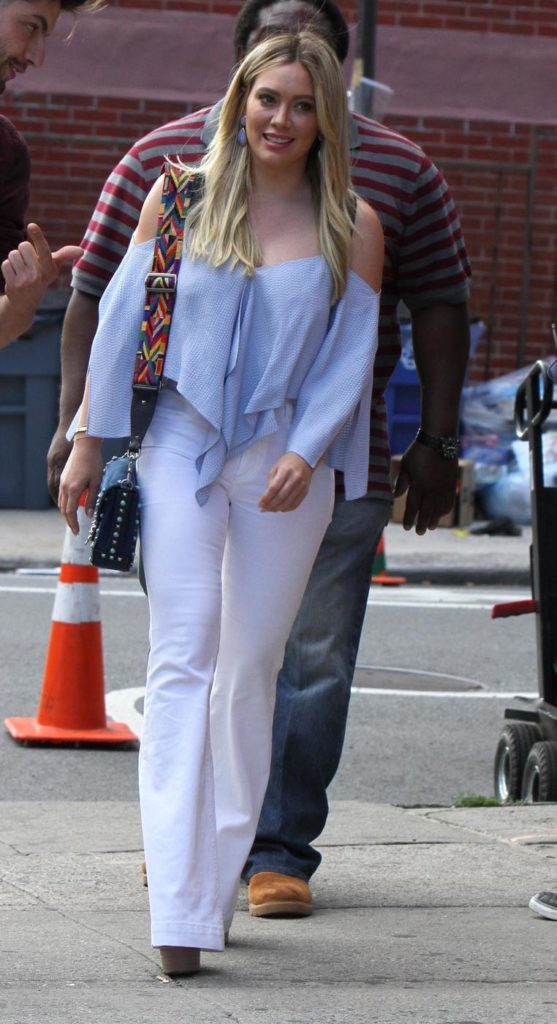 Hilary Duff wearing an off shoulder blue top, white flared jeans, and chunky heels