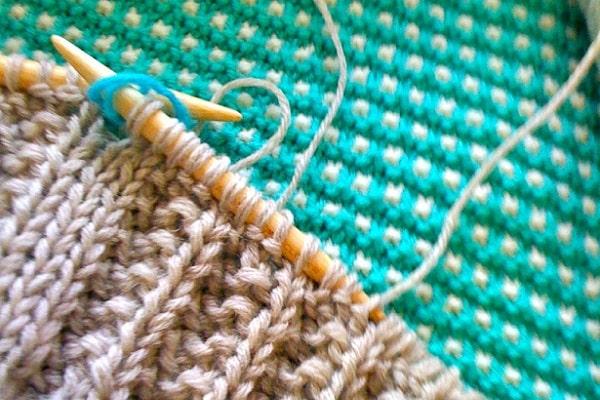 knitting dusty pink yarn on aqua
