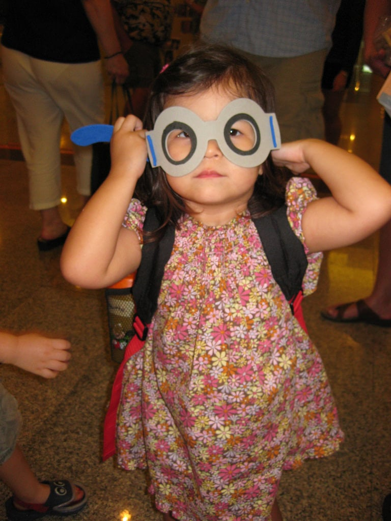 A little girl wearing a pair of paper glasses
