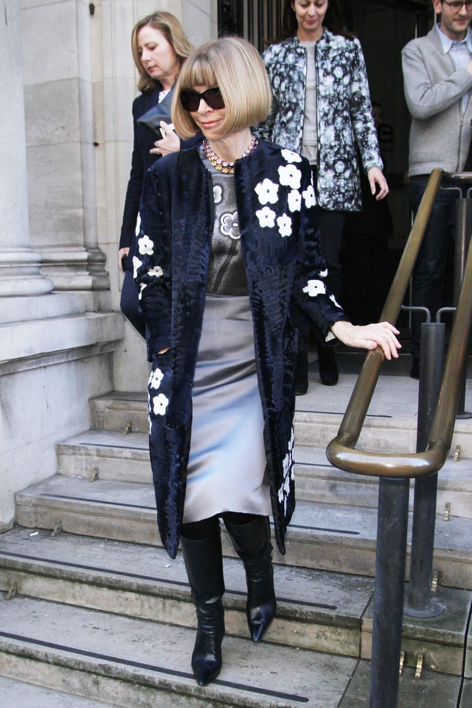 Anna Wintour wearing a gray satin pencil skirt, a gray floral top, a black and white floral fur coat, and a statement necklace with boots
