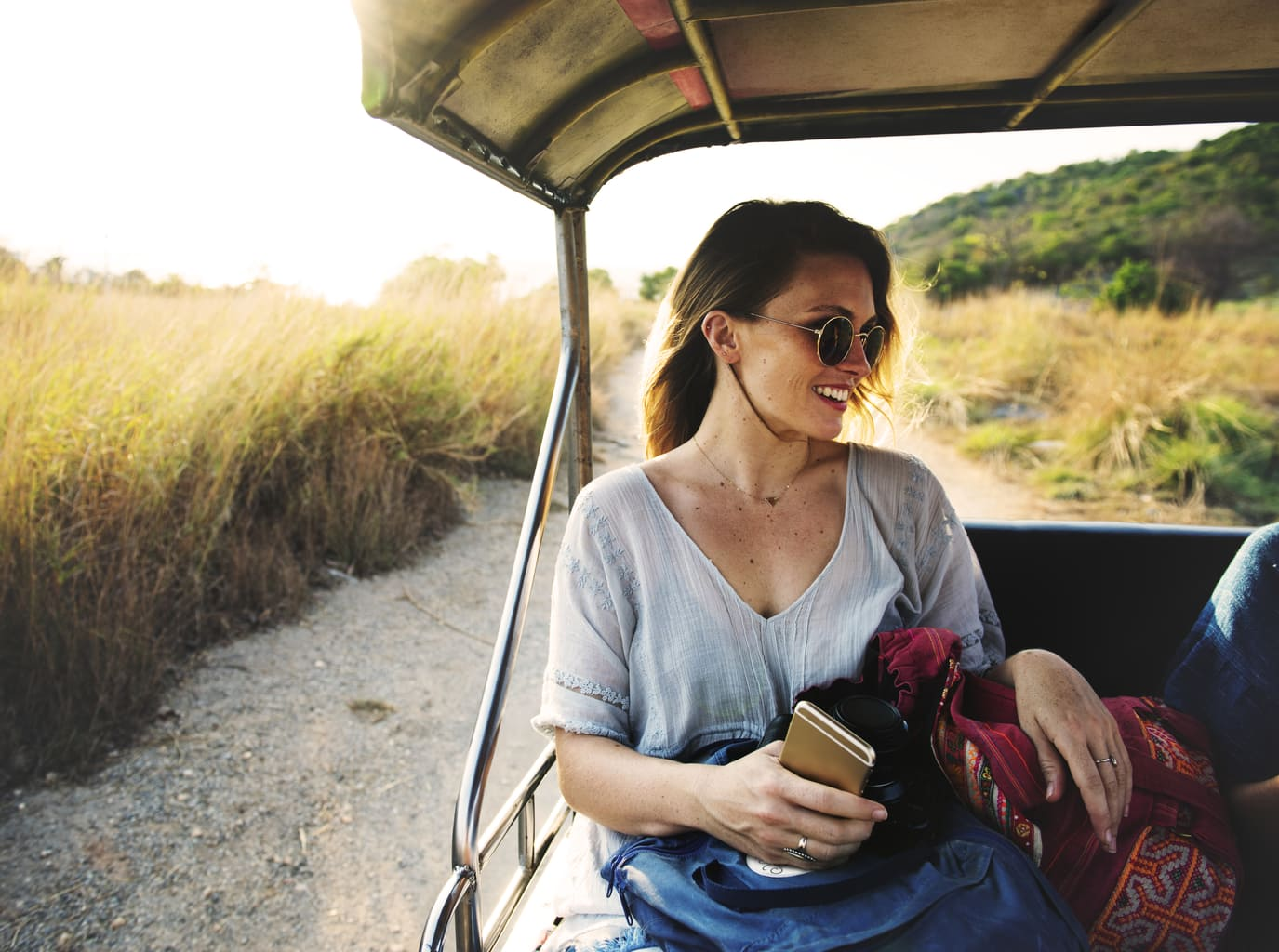 Photo of girl wearing glasses and holding an iPhone in the back of a cart.