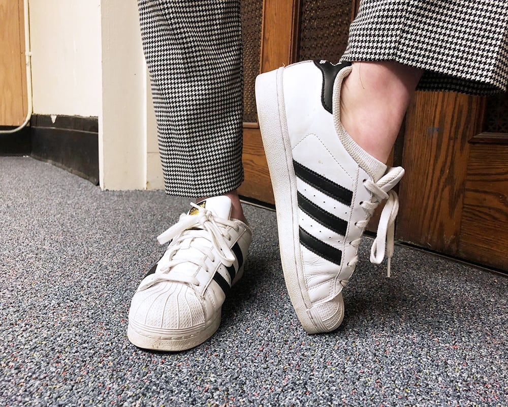 Rachel wears classic white Adidas Superstar sneakers.