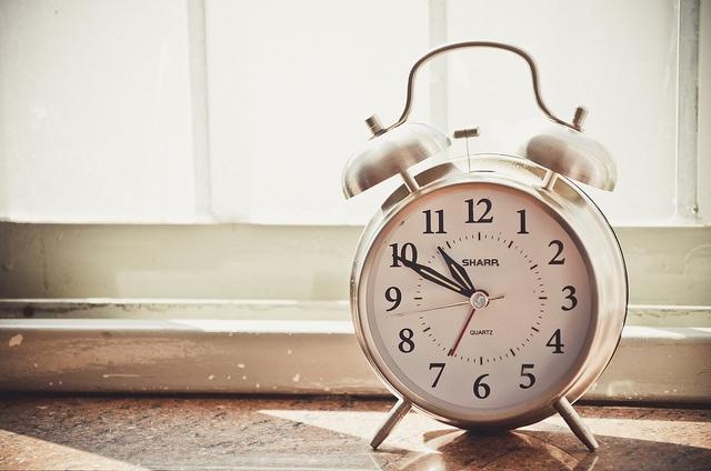 Silver alarm clock sitting by window