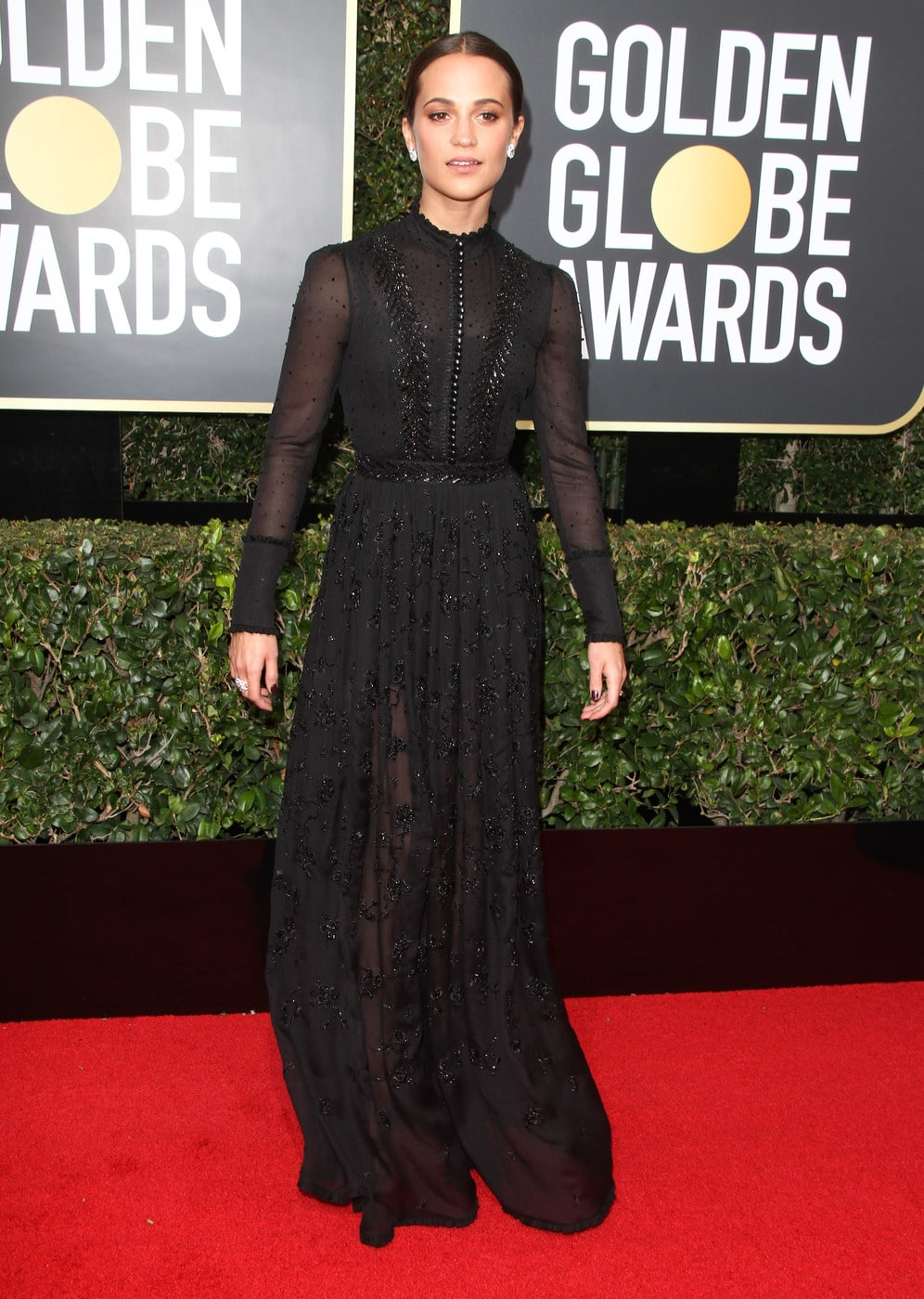 Alicia Vikander in a long sleeved Victorian influenced Louis Vuitton gown in black at the 2018 Golden Globe Awards red carpet