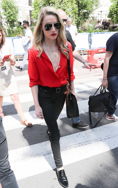 Amber Heard wearing aviator sunglasses, layered gold necklaces, a red button-down shirt, black skinny jeans, a black long strap bag, and black Oxford shoes