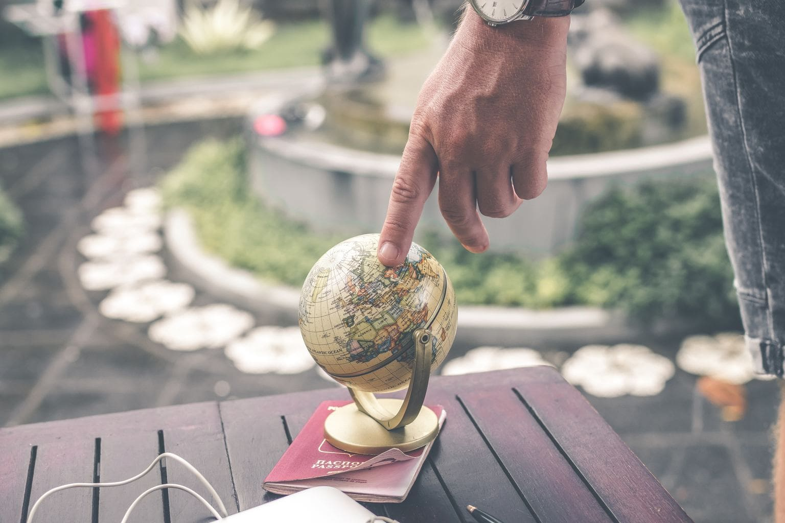 Person touching a globe with their finger.