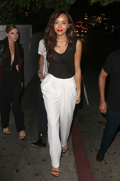 Ashley Madekwe in white trousers, a black tank top, and a red lip