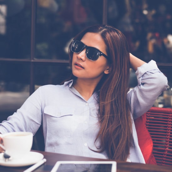 Photo of a young woman wearing sunglasses and a button-up shirt, sitting at a table in a cafe holding a coffee cup