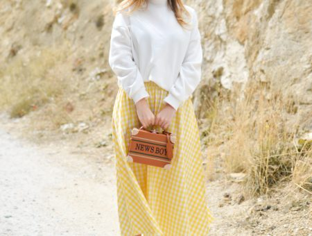 Photo of woman standing against rocky background wearing yellow dangling earrings, white turtleneck top, yellow and white gingham skirt, and pale pink heeled sandals, holding a cognac brown box bag that says