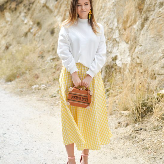 "Photo of woman standing against rocky background wearing yellow dangling earrings, white turtleneck top, yellow and white gingham skirt, and pale pink heeled sandals, holding a cognac brown box bag that says ""NEWS BOY"""
