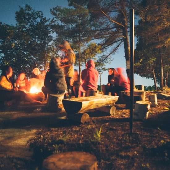 Photo of a group of people sitting around a campfire in the woods by the water at twilight