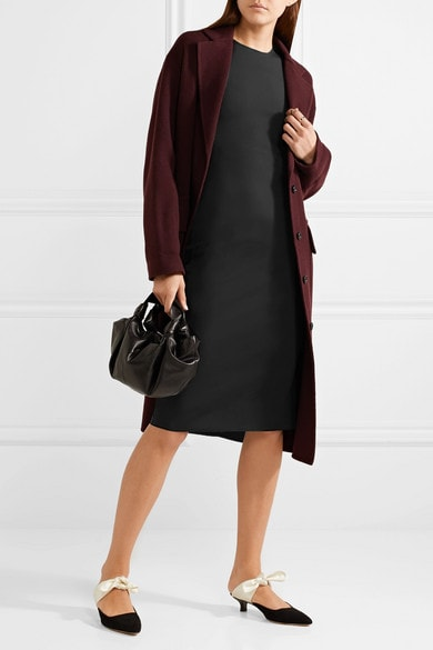 Woman wearing black sheath dress, maroon coat, and black pointed-toe kitten-heel mules with white bow, and carrying small black leather bag