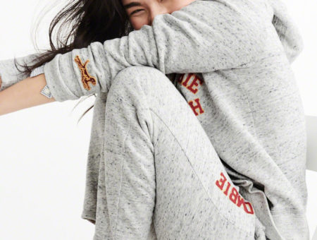 Woman sitting down on a white chair with her knees drawn close to her body wearing matching light heather gray sweatpants and sweatshirt with Abercrombie & Fitch logo in red outlined in yellow and dog on sweatshirt sleeve, with the sleeve of a  blue-and-white button-up shirt peeking out from under one of the arms of the sweatshirt