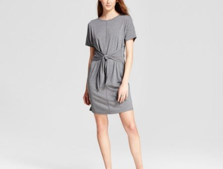 Woman wearing gray short-sleeved t-shirt dress with front tie and black sneakers