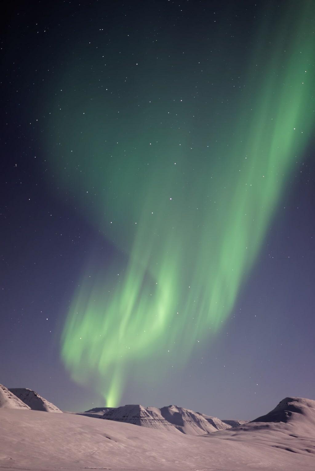 Aurora borealis in the sky over desert mountains