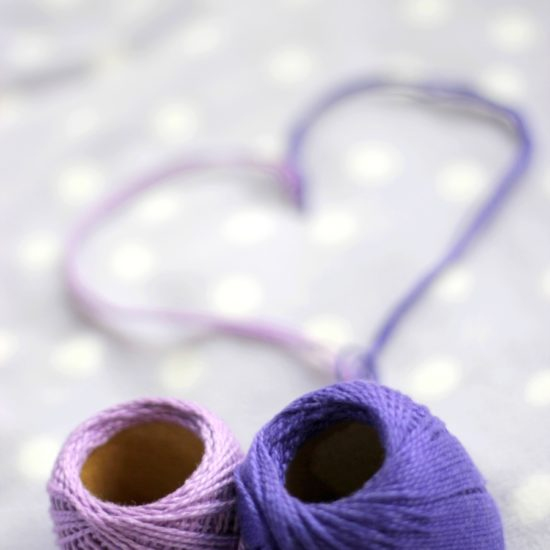 Balls of yarn in purple creating a heart