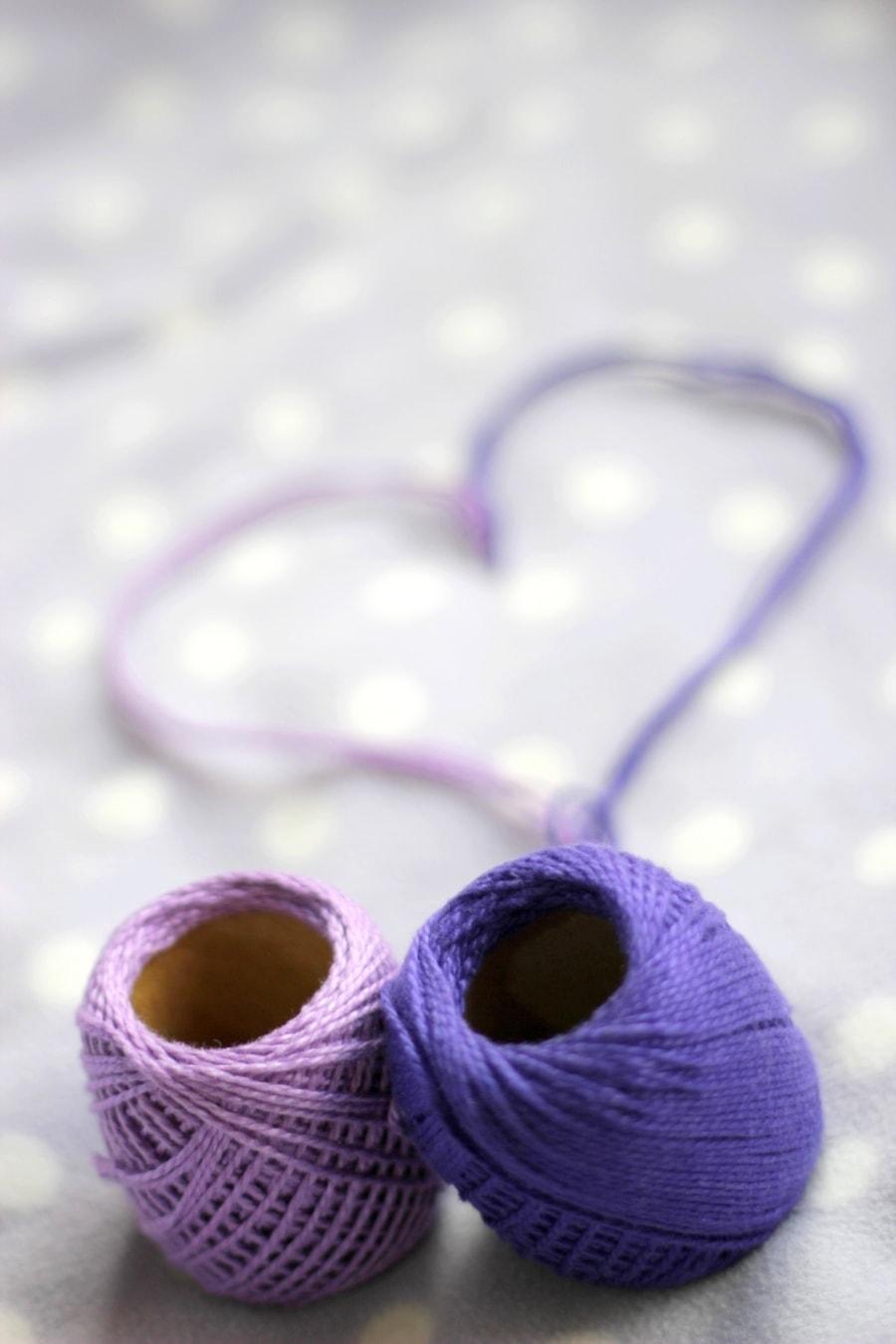 Balls of yarn in purple creating a heart