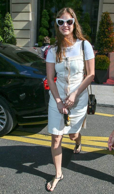 Barbara Palvin wearing a white t-shirt under a cream button-front dress with a square neckline, oversized white cat-eye sunglasses, a chainlink crossbody bag, and black thong flat sandals