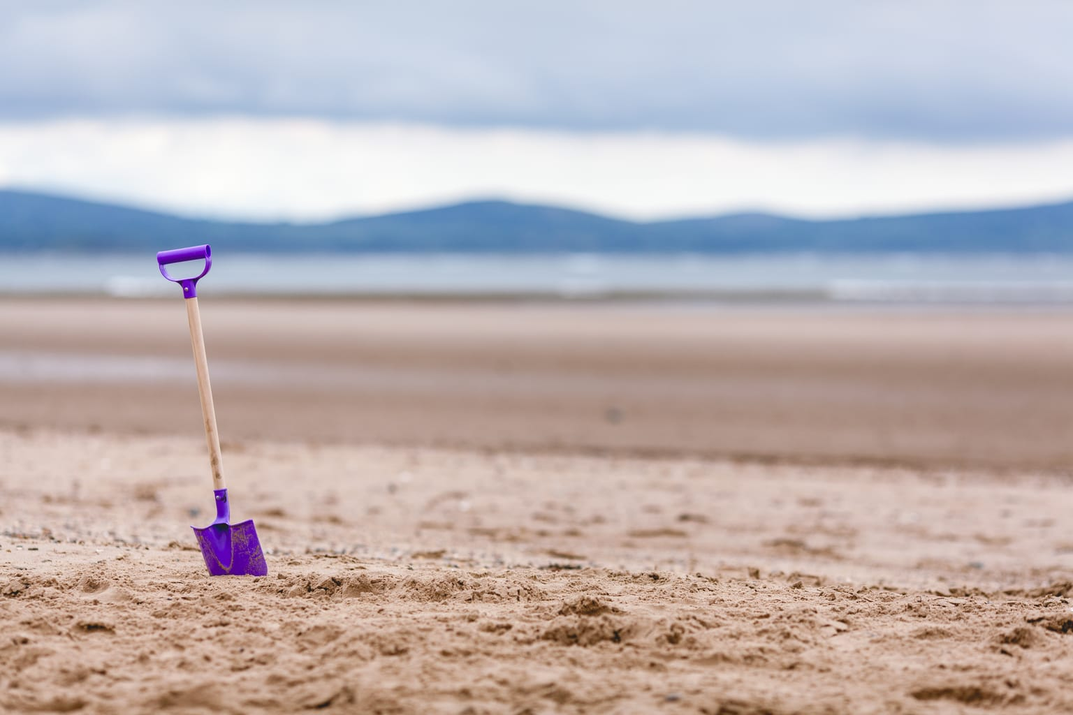 Beach activities: Fun things to do at the beach. Picture of a purple shovel in the sand at a beach.
