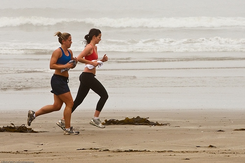 Two female joggers on foggy morro strand state beach