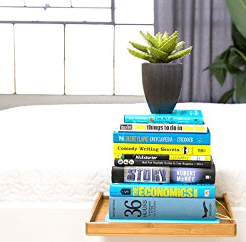 bamboo bed shelf with stacks of books and a plant on top