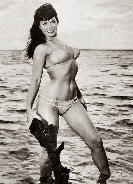 Bettie Page on beach in bikini, black and white photo
