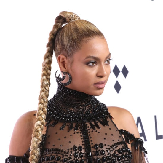 Beyonce rocking a black high neck gown, statement earrings, and a high ponytail at a Tidal event in 2016
