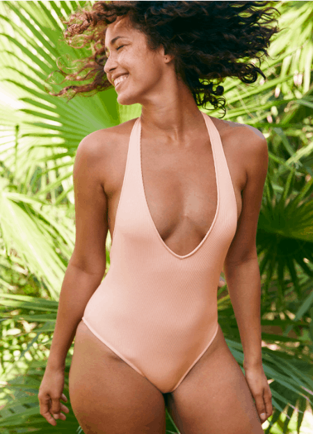 Brunette girl in front of palms wearing a peach colored one-piece bathing suit.