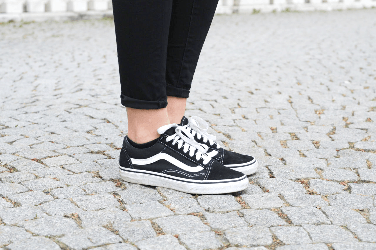 Classic black and white Vans Old Skool sneakers paired with black skinny jeans