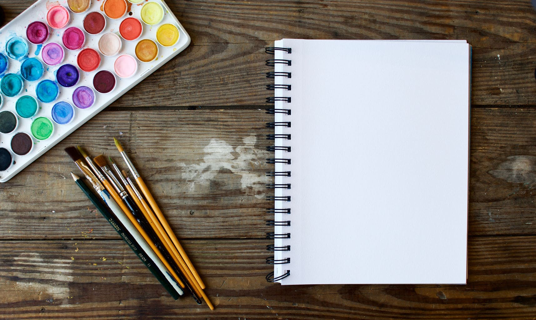 blank-notebook-with-colorful-paint-and-paint-brushes
