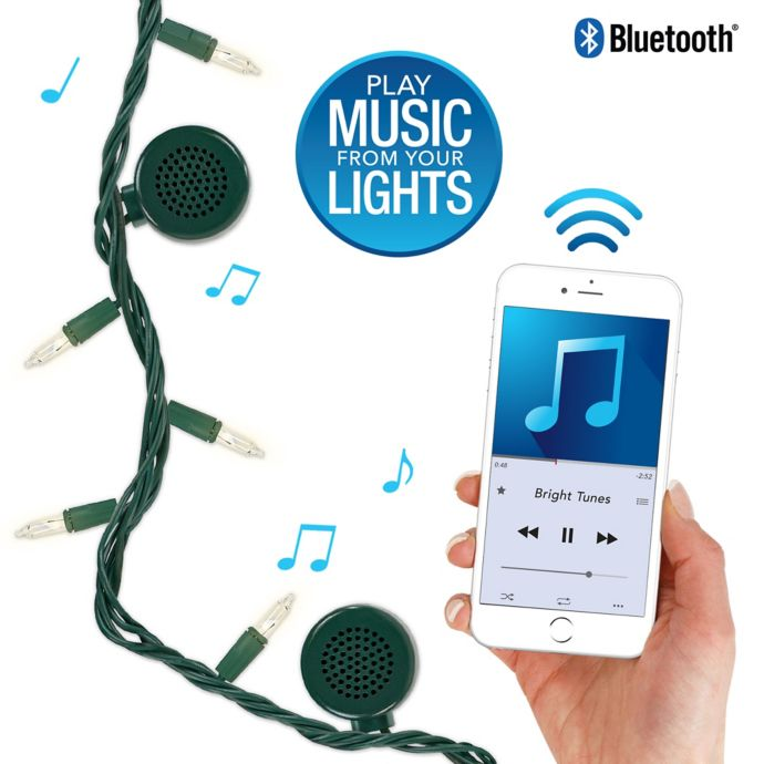 White string lights with a bluetooth speaker and music playing from the phone