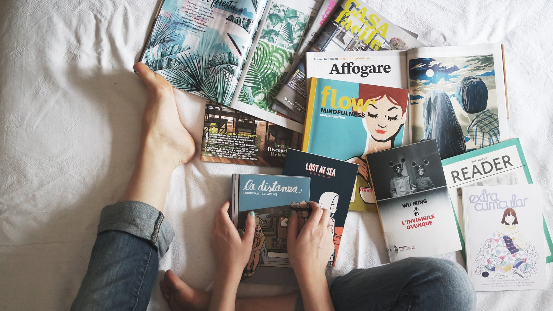 Legs wearing jeans on a bed with white sheets and a pile of colorful books of different types.