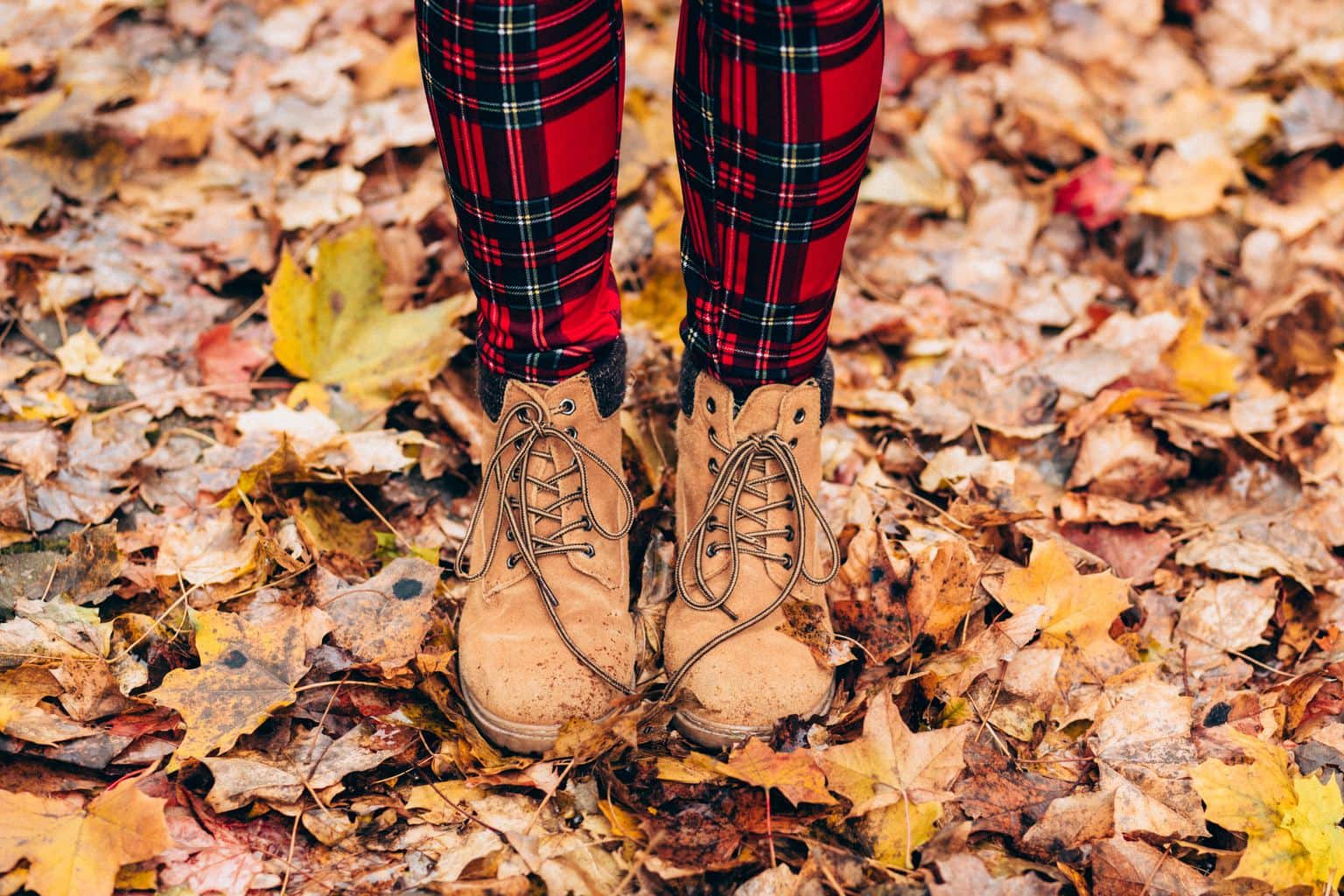 Lady's legs with red plaid leggings and tan boots amongst fallen leaves.