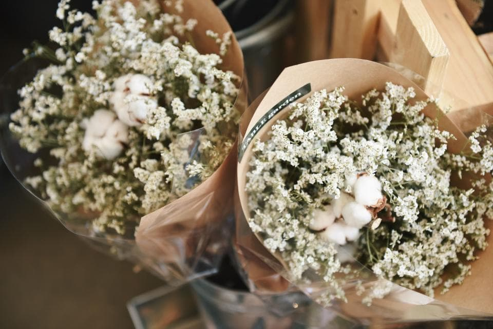 Photo of two bouquets of white flowers wrapped in brown paper and plastic.