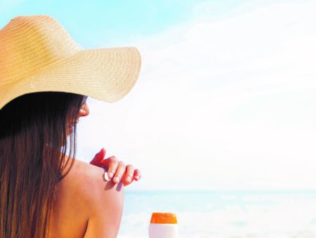 Brunette in Sun Hat Applying Sunscreen