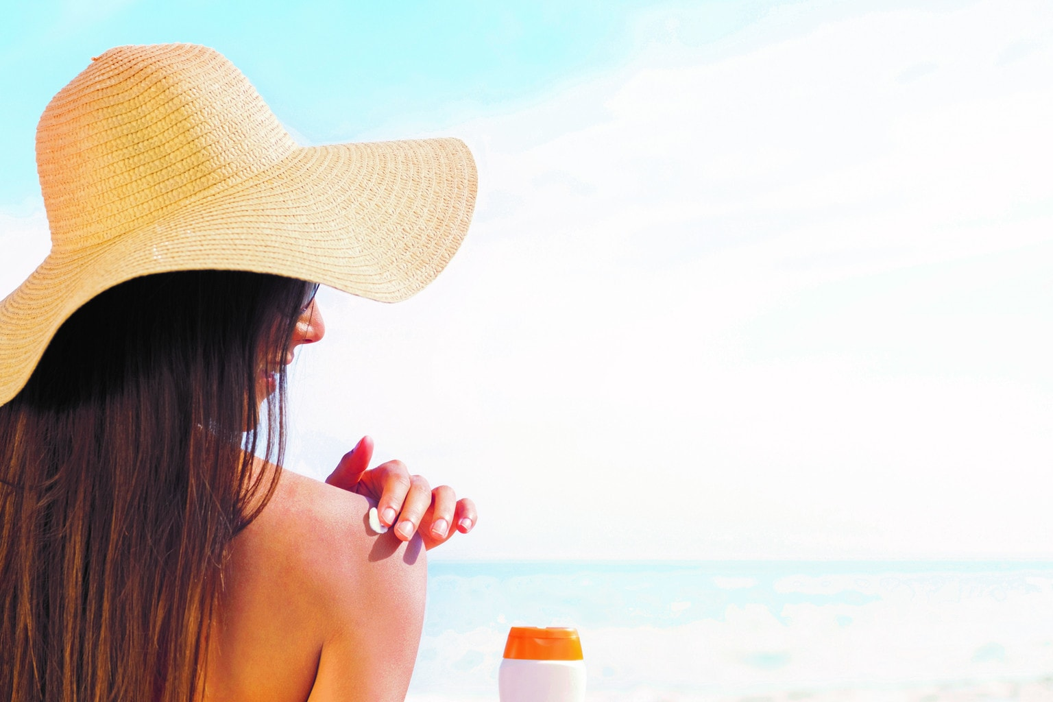 Brunette in Sun Hat Applying Sunscreen
