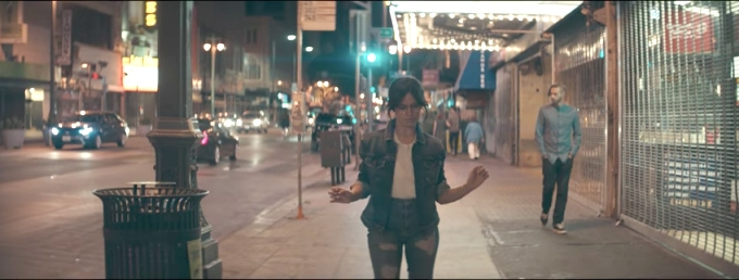 Camila Cabello in her Havana music video dancing in the street wearing jeans and a jean jacket with glasses