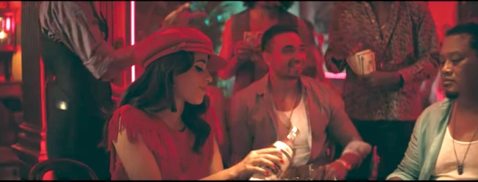 Camila Cabello in her Havana music video wearing a red dress and red hat in the club