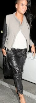 Cassie wearing leather pants, a two tone jacket, and stilettos